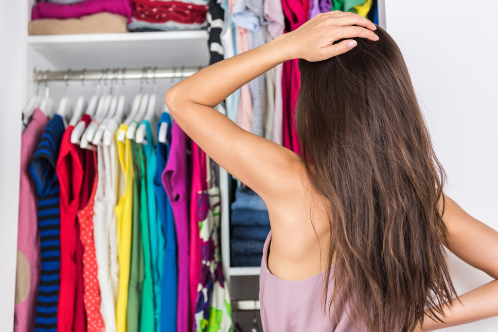 Woman looking at clothes in wardrobe scratching her head.